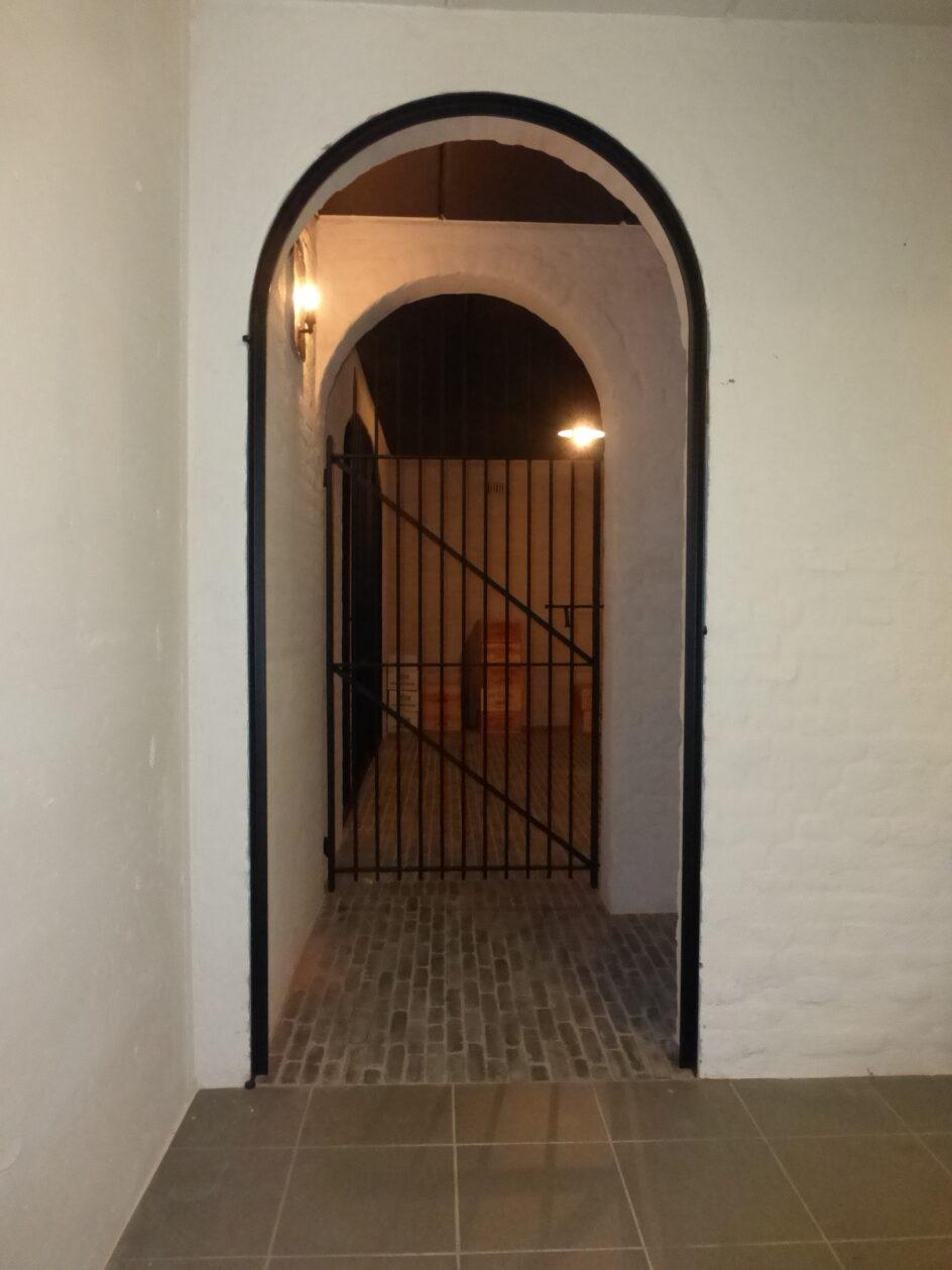 Poortje wijnkelder en gebogen deurkader voor eiken pivotdeur